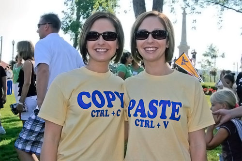 "Two wonen: one wearing a ""Copy (control + C)\"" T-shirt, the other wearing a \""Paste (control + V)\"" T-shirt."