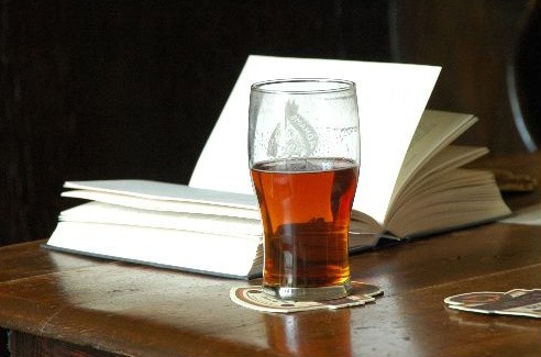A glass of beer and a book