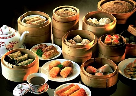 Wooden steamers and plates full of dim sum dishes