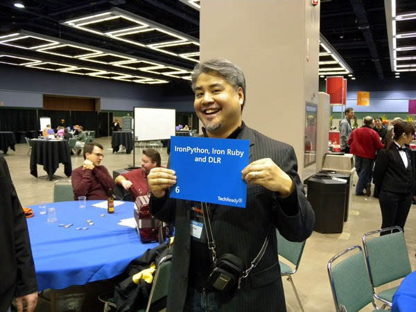 "Joey deVilla at TechReady 8, holding up an ""IronPython, IronRuby and DLR"" sign"