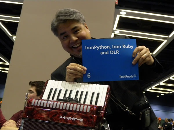 """Joey deVilla at TechReady 8, holding up an """"IronPython, IronRuby and DLR"""" sign"""