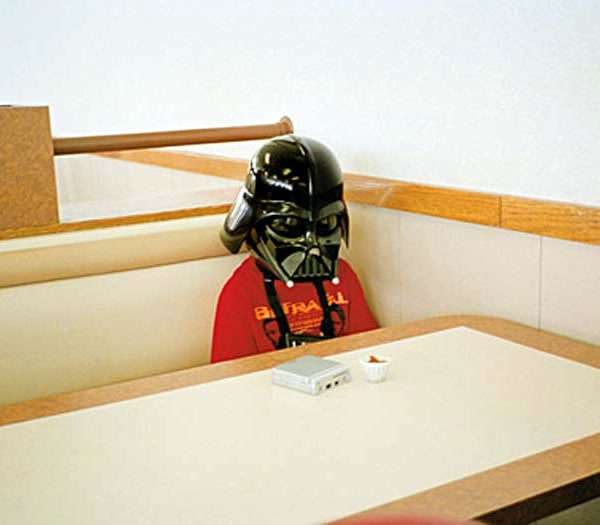 Sad-looking kid in a Darth Vader mask sitting alone at a fast-food restaurant table.