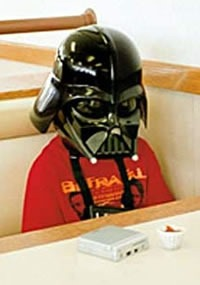 A sad-looking kid in a Darth Vader sitting at a fast food restaurant table
