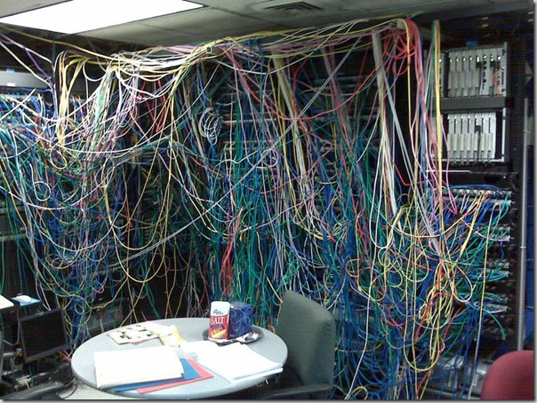 Server room, with a large tangle of wires. In the centre of the room is a table covered with folders, papers, and a large container fo salt.