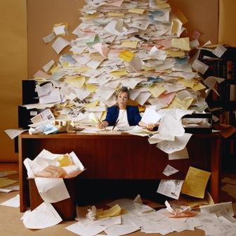 Woman at desk overwhelmed by a pile of paper