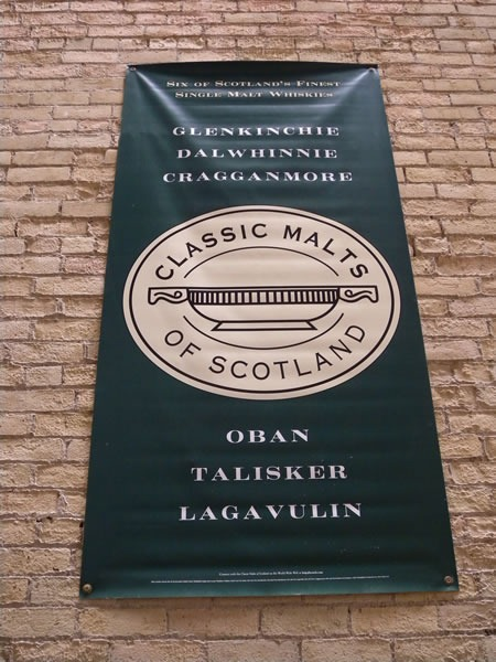 "Banner on brick wall: ""Classic Malts of Scotland: Glenkinchie, Dalwhinnie, Cragganmore, Oban, Talisker, Lagavulin"""