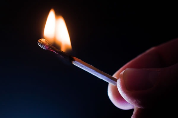Fingers holding a lit match