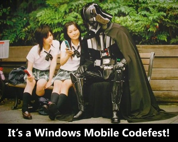 Two Japanese schoolgirls showing off their cellphones to Darth Vader