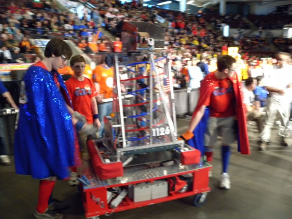 team_in_capes_carrying_robot