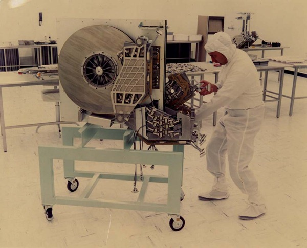 "Late '60s/early '70s photo of man in ""clean suit"" pushing a giant hard drive on a cart in a computer room."