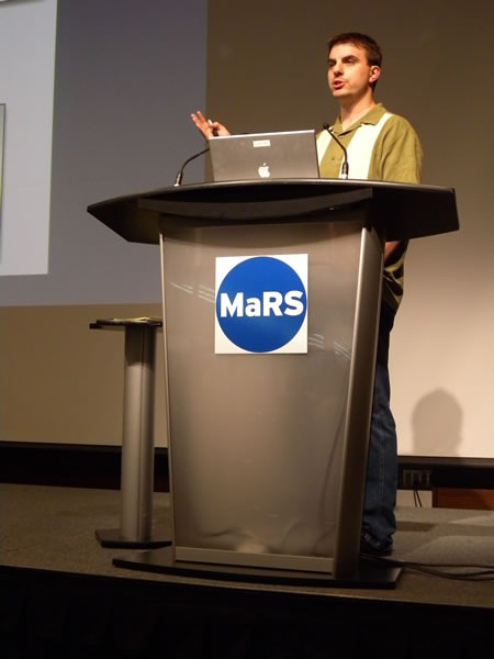 Titus Brown at the podium at MaRS