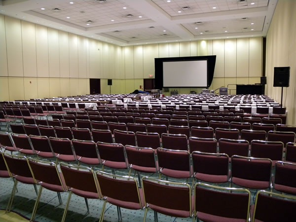 View of a large presentation room, as seen from the back.