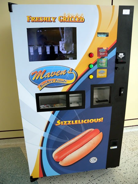"The hot dog vending machine at the Metro Toronto Convention Centre. Its signs say: ""Freshly grilled / Maven's Kosher Foods / Sizzlelicious!"""