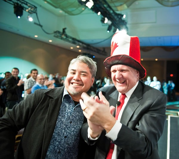 Joey deVilla and Steve Ballmer, wearing Joey's Canadian flag raver hat