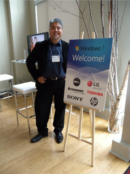 "Joey devilla, standing beside a ""Windows 7: Welcome!"" sign"