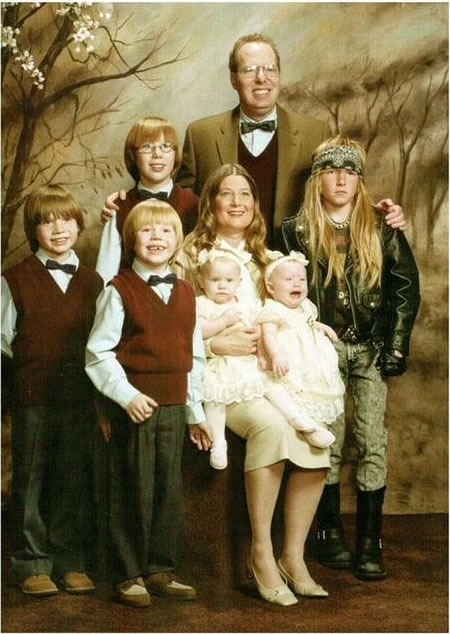 Family photo with everyone in the Sunday best, except for a son wearing metal/biker gear.