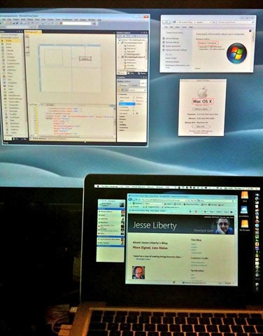 A MacBook Pro standing in front of a Cinea Display monitor, showing both Windows 7 and Mac OS X.
