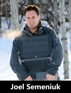 Photo of Joel Semeniuk standing outside with his laptop on a very cold winter day