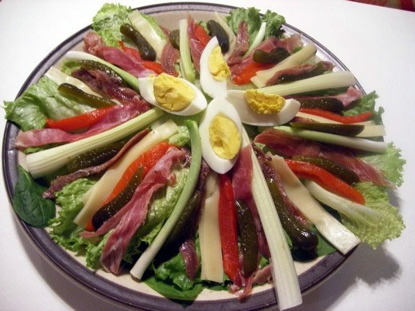 A salmagundi made of hard-boiled eggs, lettuce, cheese, red peppers, meat and pickles.