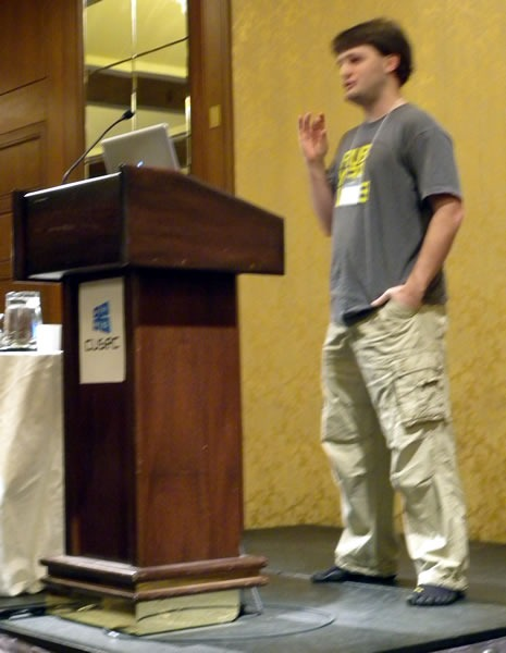 Matt Knox, standing at the lectern, delivering his keynote at CUSEC