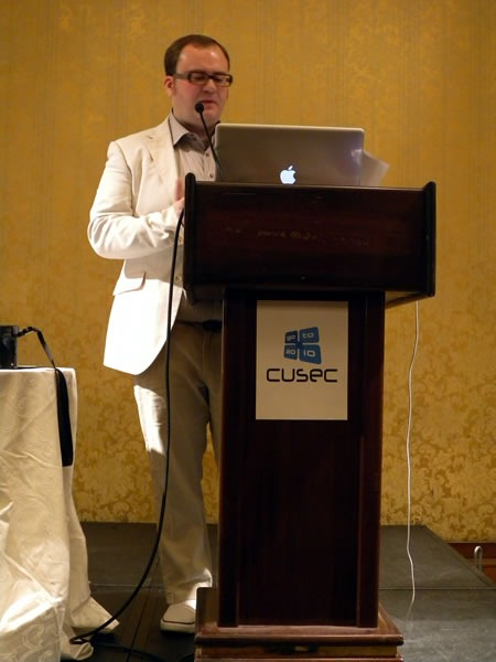 Pete Forde, standing at the lectern, giving his keynote at CUSEC 2010