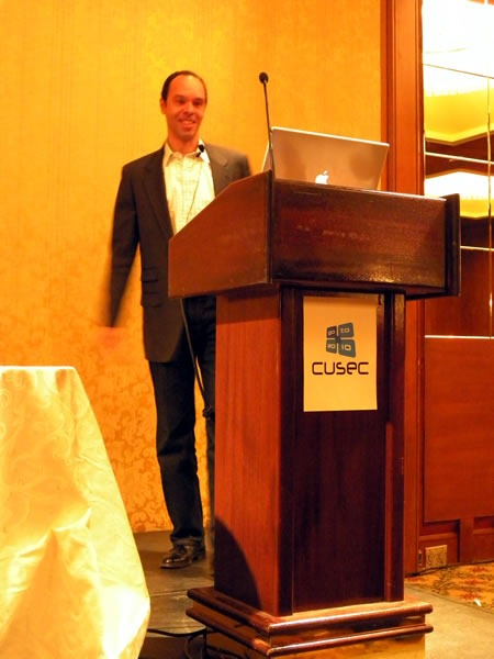 Reg Braithwaite, standing at the lectern, giving his keynote at CUSEC 2010