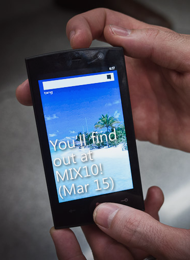"Hands holding Win 7 Phone that reads ""You'll find out at MIX10! (Mar 15)"""