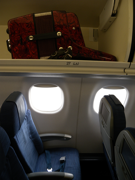 Joey deVilla's red Silvetta accordion in the overhead bin above his airplane seat