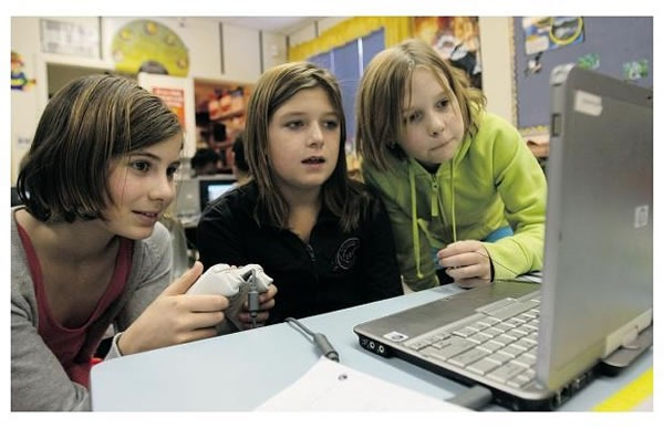 Three Students at St. Mary Catholic Elementary School programming with Kodu.