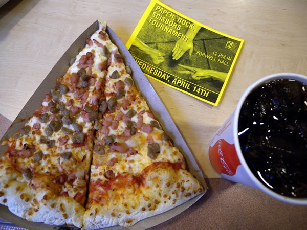 "Slice of pizza, glass of coke and a flyer for a ""Rock/Paper/Scissors tournament"""