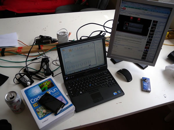 "HacklabTO work table with my laptop plugged into a monitor, mouse, ""Coding4Fun"" book and can of Diet Coke"