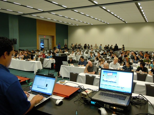 Photo of the session room, with Mark Arteaga setting up his computer in the foreground