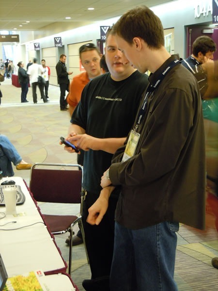 Barranger Ridler and Cory Fowler demonstrating Windows Phone 7 to a booth visitor