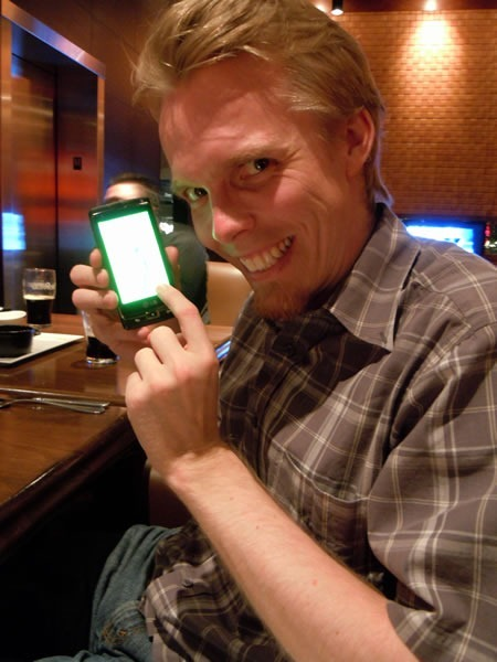 Morten Rand-Hendriksen smiles maniacally as he holds a Windows Phone 7 device