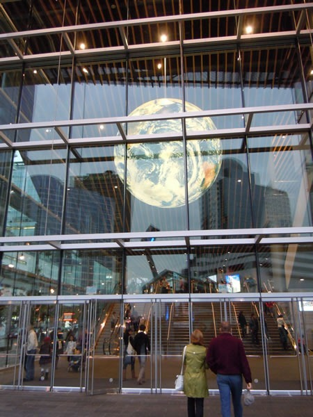 Burrard Street doors to Vancouver Convention Centre's West Building, with the giant globe hanging from the ceiling visible through the glass walls