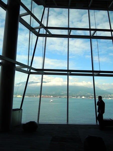 A silhouetted TechDays attendee takes a phone call against the north windows of the Vancouver Convention Centre's West Building, with the oceans and mountains in the background