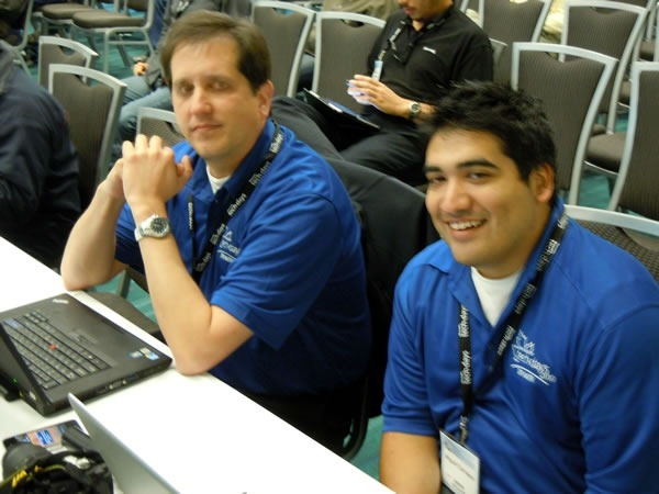 Aaron Kowall and Miguel Carrasco, seated and watching a presentation
