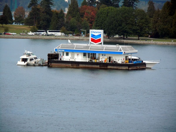 A floating chevron gas station, with a couple of boats moored to it