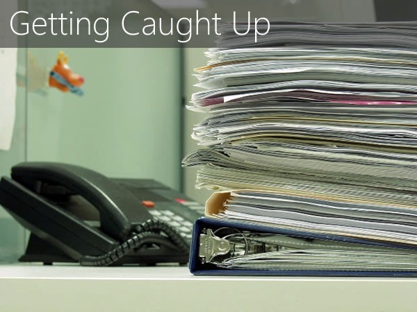 """Getting Caught Up"": Large stack of papers in an office cubicle"