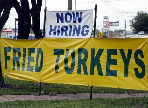 "Two signs, one atop the other. Top sign: ""Now hiring"". Bottom sign: ""Fried turkeys"""