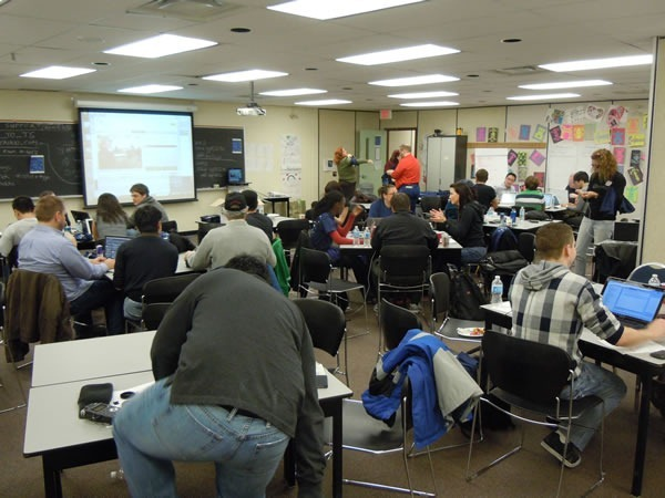 The main RHoK room as seen from the back, packed with developers working at various tables