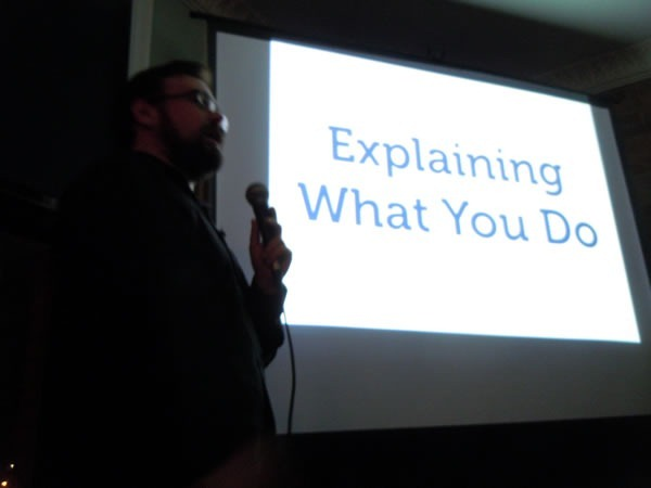 "Yehuda Katz giving his presentation with a slide in the background that reads ""Explaining What You Do"""
