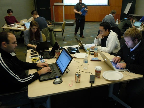 Four developers working on their laptops, gathered around a single table