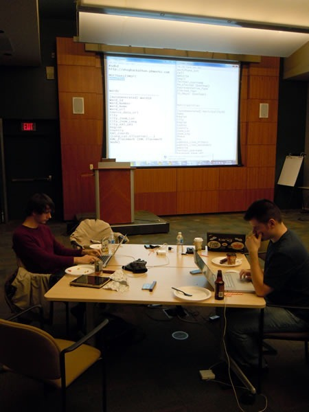 Two developers working on an open data problem, with a large project in the background