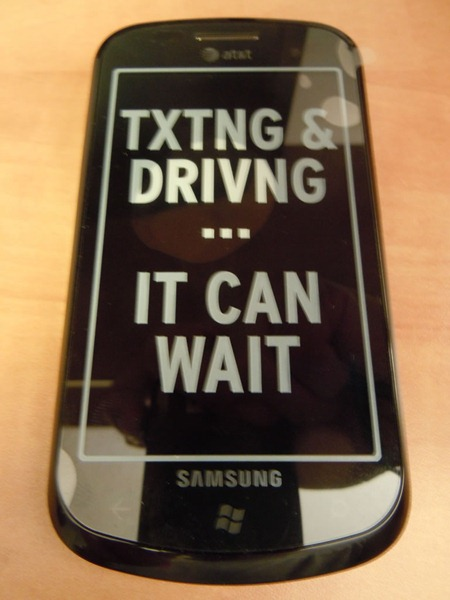 "Front of Samsung Focus phone, with ""TXTING & DRIVNG...IT CAN WAIT"" sticker"