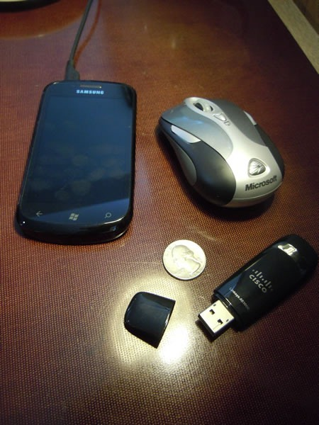 The Cisco Linksys AE1000 beside a Samsung Focus phone, US quarter and Microsoft Presenter Mouse