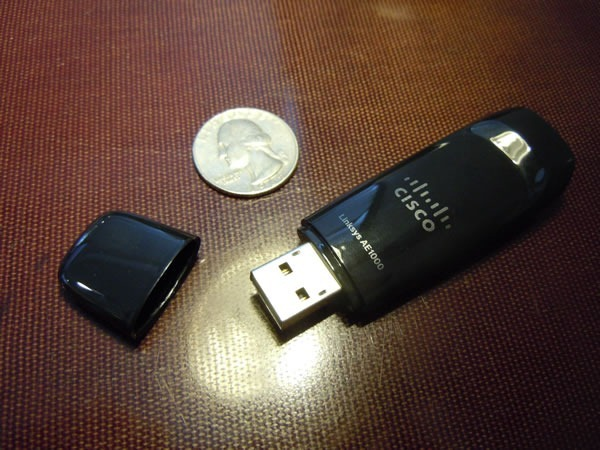 Cisco Linksys AE1000 dongle, with its cap off, placed beside a US quarter