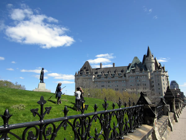 Groundskeepers raking up stray grass on Parliament Hill, with Chateau Laurier in the background