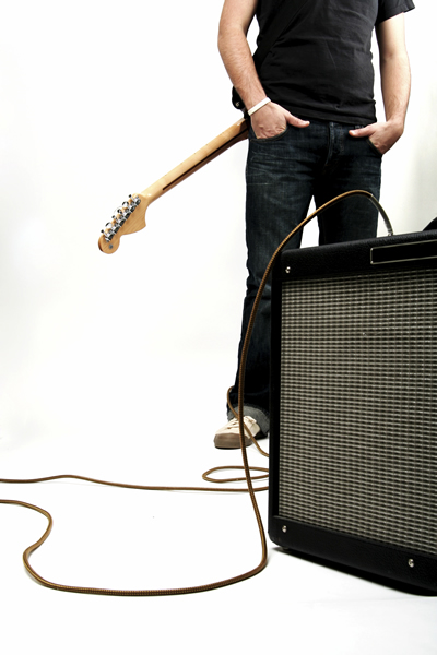 Neck-down shot of a guy with guitar and amp