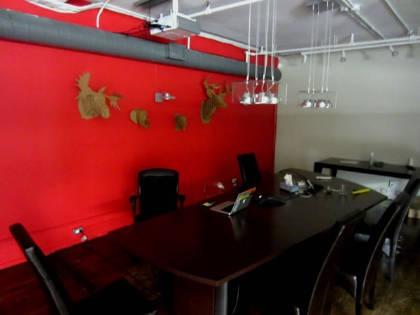 "Shopify's boardroom, with cardboard animal ""trophies"" hanging on the far wall"